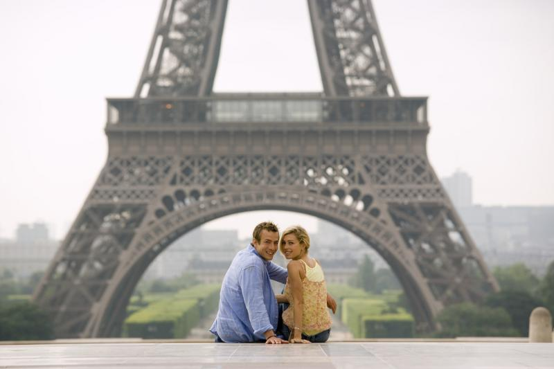 Paris tour from London with couple sitting at Eiffel Tower
